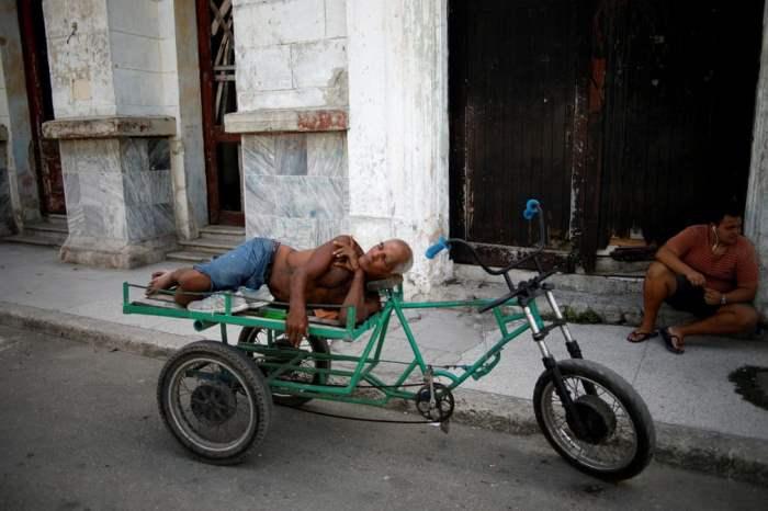 Мужчина дремлет на трехколесном велосипеде
