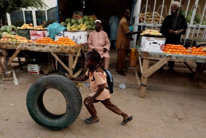 Мальчик катит шину на рынке