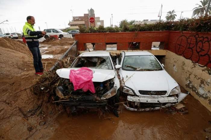 Мужчина фотографирует поврежденные машины