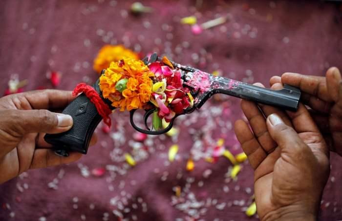 Полицейский возносит молитвы на свое оружие