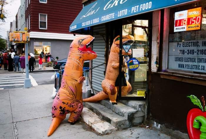 Двое детей в костюмах динозавров