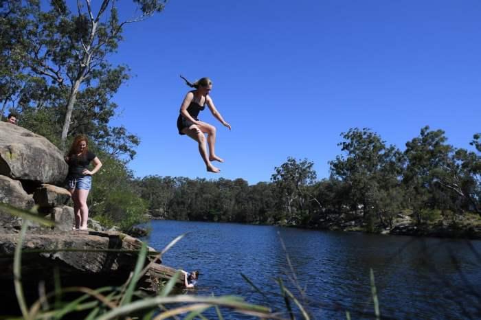 Женщина прыгает в озеро