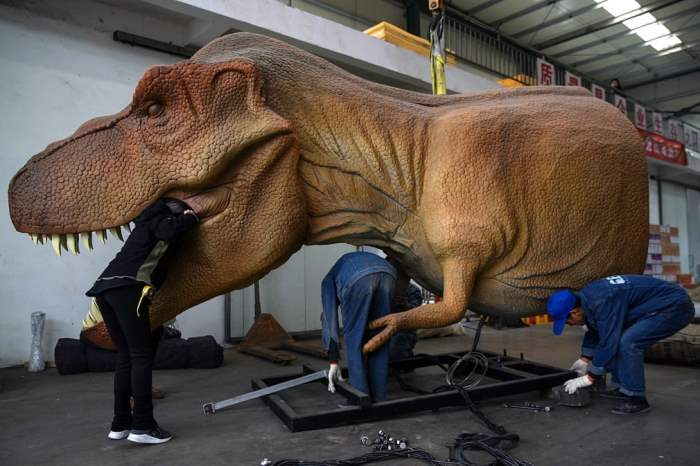 Рабочие обслуживают роботизированного динозавра