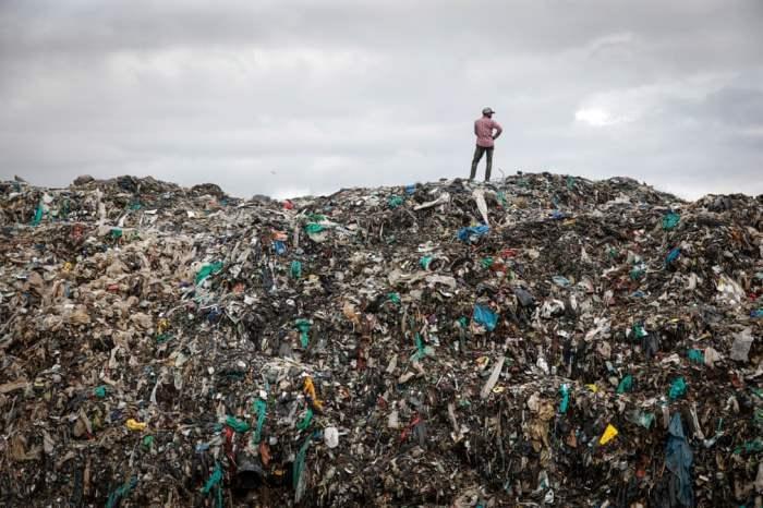 Мужчина стоит на вершине горы мусора