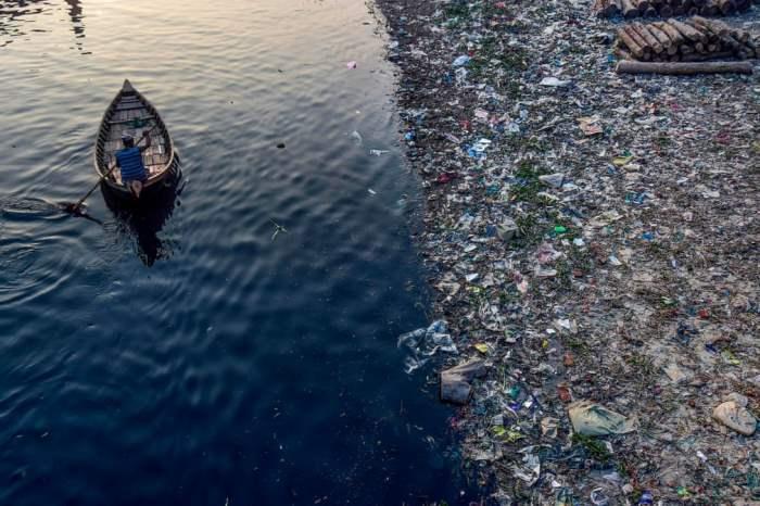 Мужчина проплывает мимо пластикового мусора