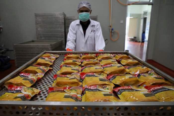 Рабочий сортирует пакеты с едой