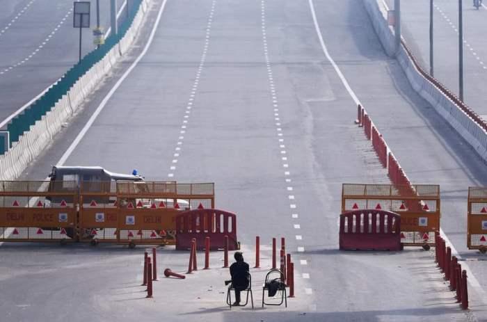 Мужчина сидит на пограничной баррикаде