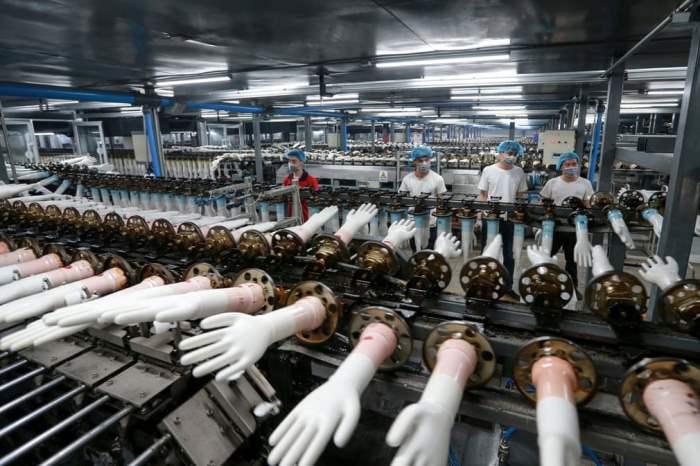 Рабочие производят медицинские перчатки