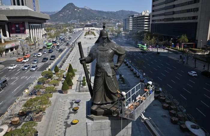 Рабочий очищает статую