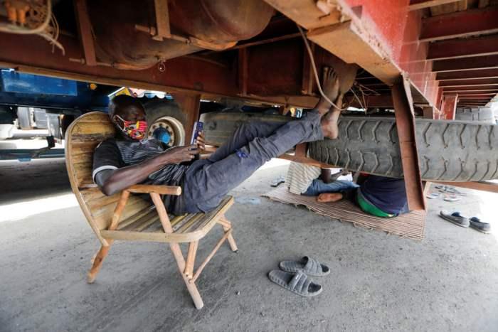 Водитель отдыхает под своим грузовиком