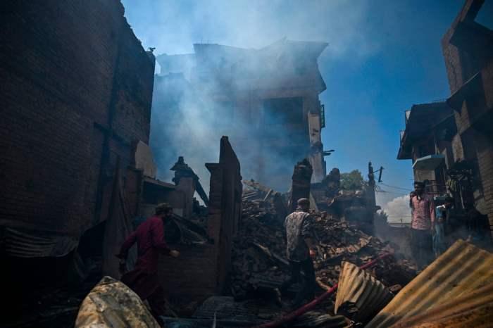 Жители собираются вокруг обломков дома