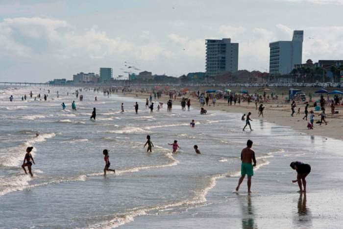 Люди наслаждаются солнечным днем на пляже Галвестон