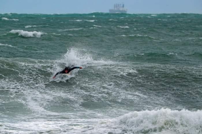 Серфер на пляже Коттесло