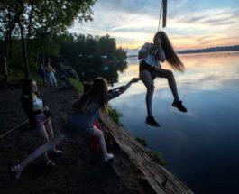 Группа друзей качает девушку на веревке