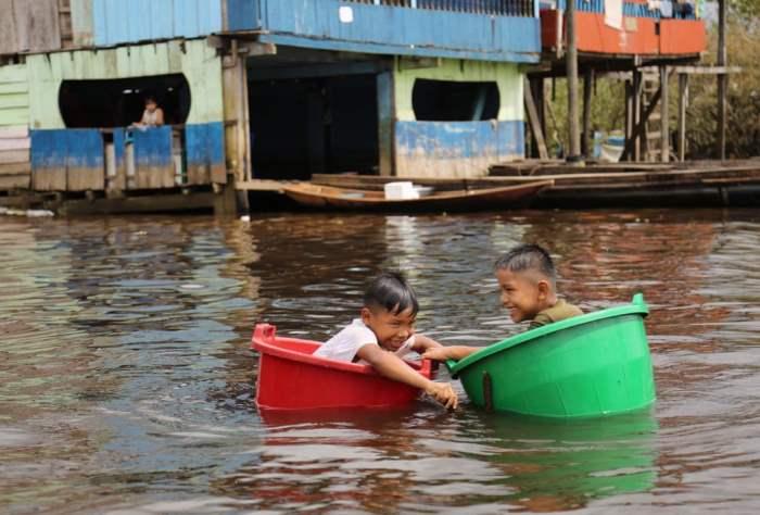 Дети плывут вдоль реки Амазонки