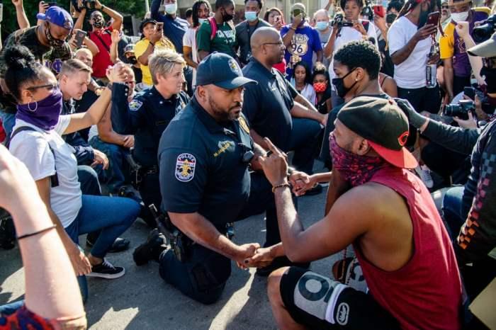 Протестующий разговаривает с полицейским