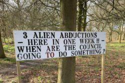 Надпись на знаке: «Три похищения инопланетянами в Седжли за неделю — но совет ничего не делает»